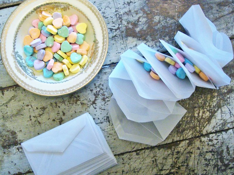 Vellum envelopes stuffed with candy hearts...