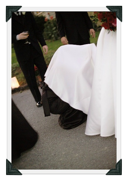 bridesmaid under wedding dress trying to bustle.