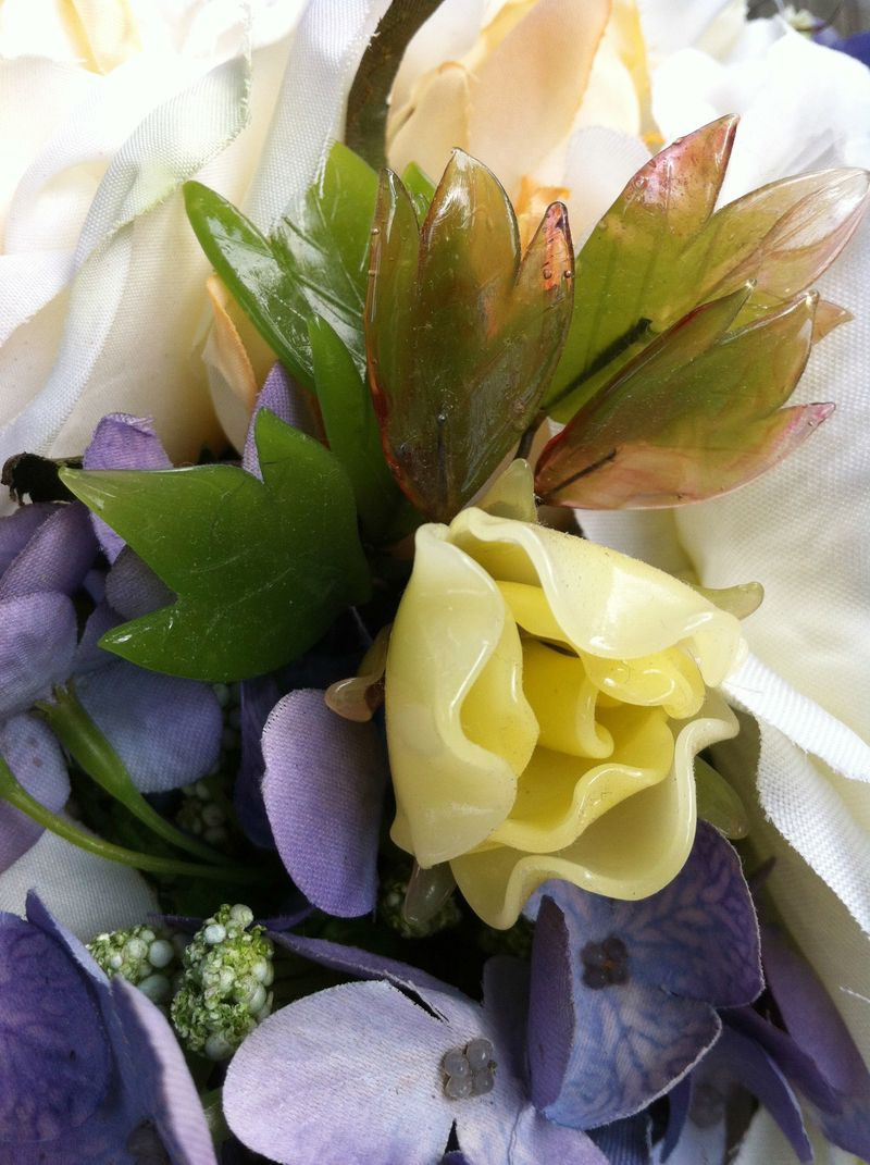Detail of vintage glass bonsai flower tucked into a bridal bouquet