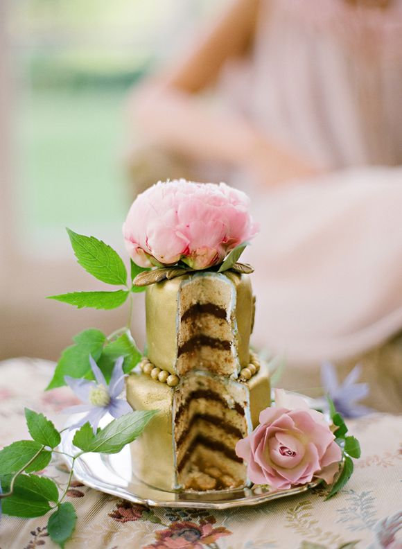 Amazing little gold wedding cake with fresh flowers and vines.